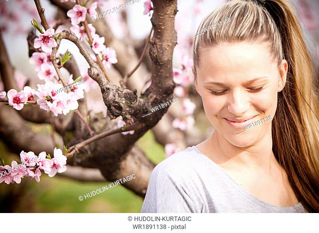 Woman with eyes closed, cherry blossom in background, Austria