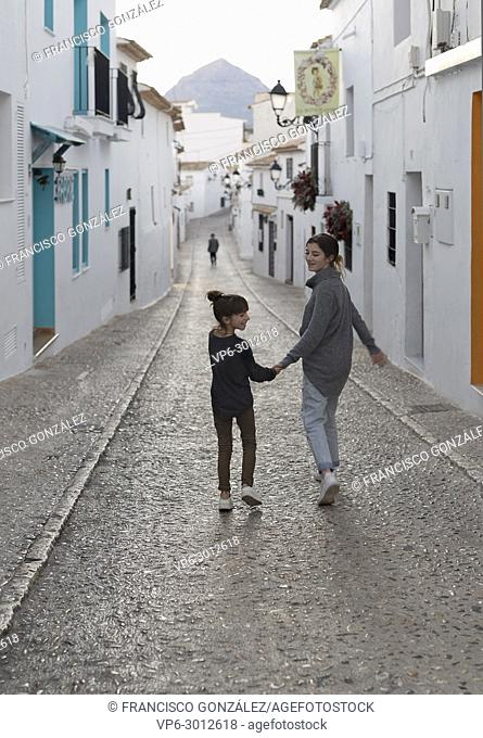 Two Sisters walking hand in hand through the town of Altea in the province of Alicante, Spain