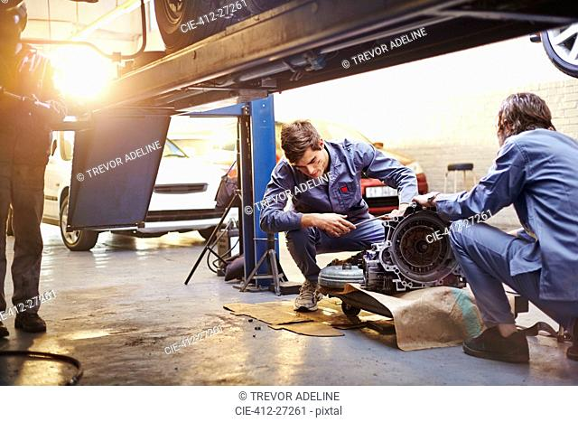 Mechanics examining part in auto repair shop