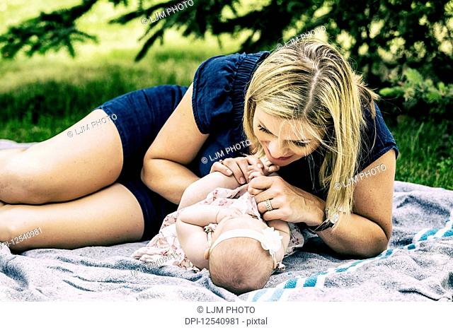 A young mother playing with her baby on a blanket in a city park on a warm summer day; Edmonton, Alberta, Canada