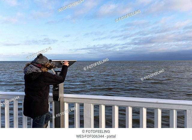 Germany, Cuxhaven, Tourist looking through binoculars