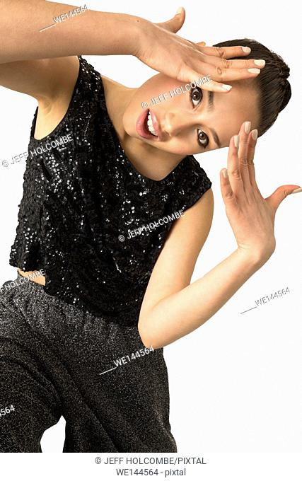 Attractive young woman dancing nearly full length, in elegant but edgy, hip-hop style in studio shot on white background