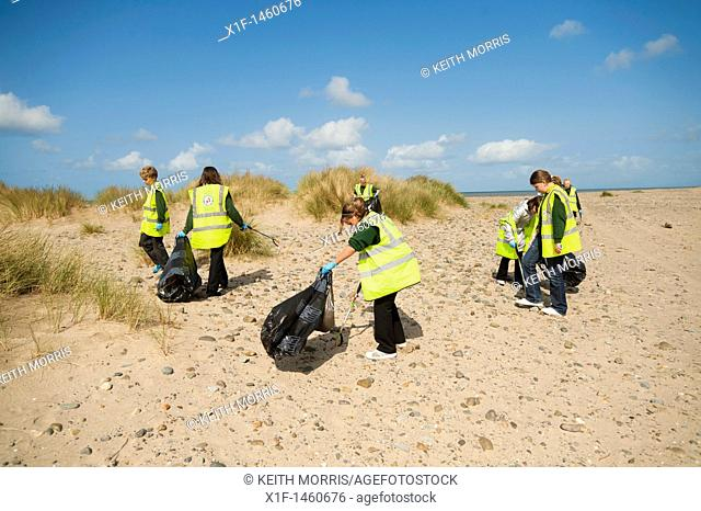 Primary school children collecting litter on the beach at Barmouth, Gwynedd, north wales, UK