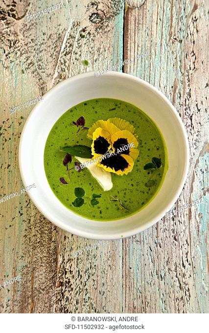 Cold pea soup with edamame beans, basil, mint and pansies