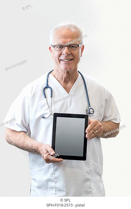Senior male doctor holding digital tablet, portrait