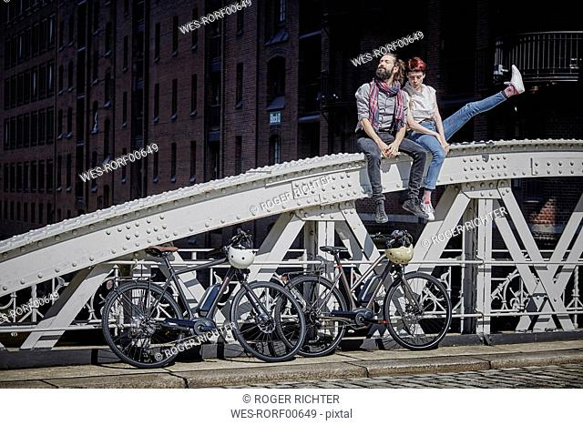 Germany, Hamburg, couple with electric bicycles sitting on railing of a bridge