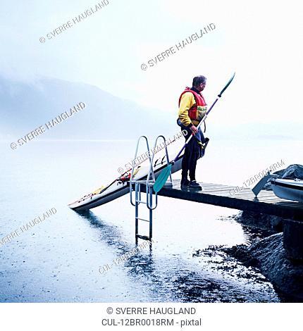Man pulling kayak onto dock