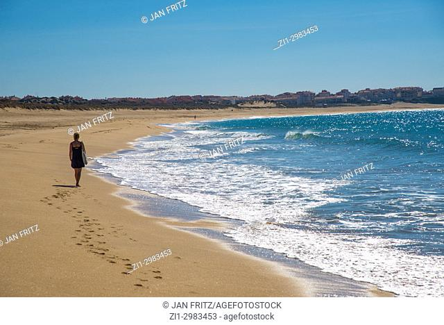 woman walking at the empty beach in the Bay of Peniche, Portugal