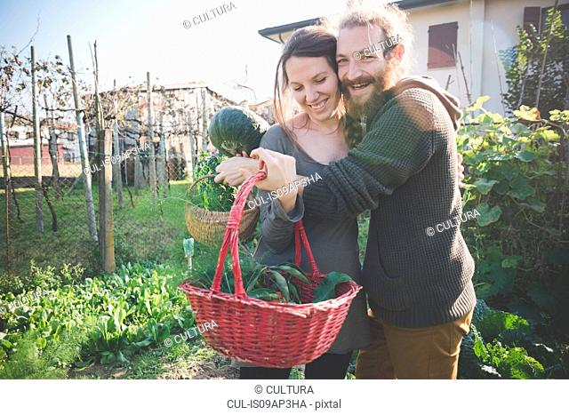 Young couple with basket of homegrown vegetables