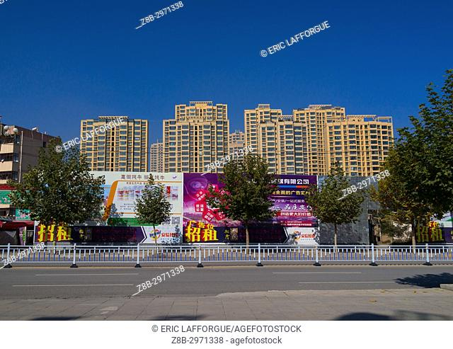 Huge advertising billboards in front of new hirise buildings, Gansu province, Linxia, China