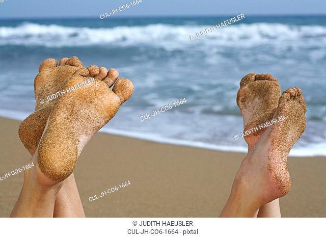 Pair of sandy feet on beach
