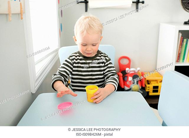 Young boy sitting at table, opening tub of pink dough
