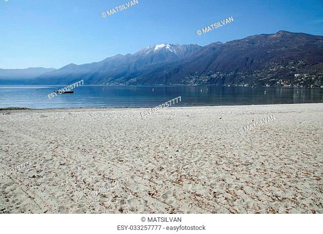 Sand beach on an alpine lake with snow-capped mountains