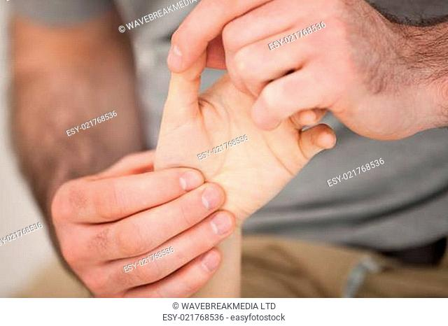 Physiotherapist palpating the fingers of a patient in a room