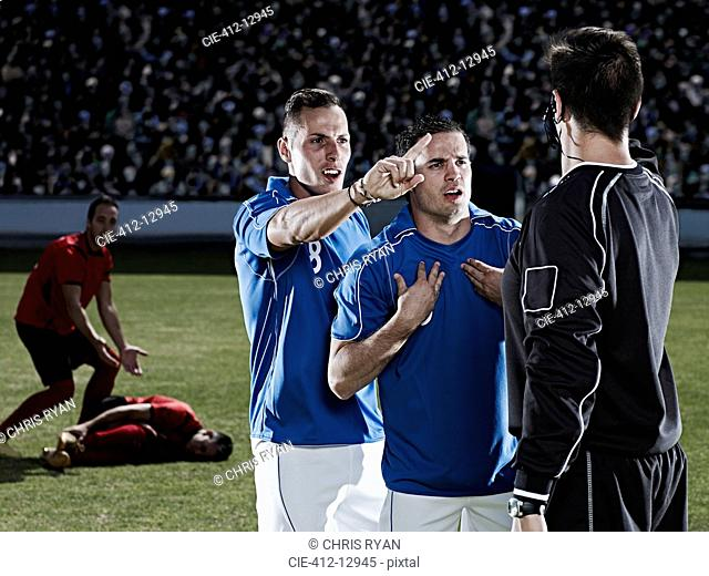 Soccer players arguing with referee on field