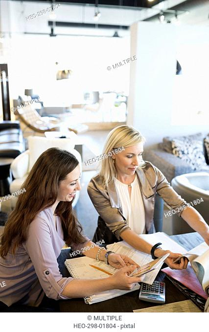 Interior designer and woman discussing fabric swatches in home furnishings store