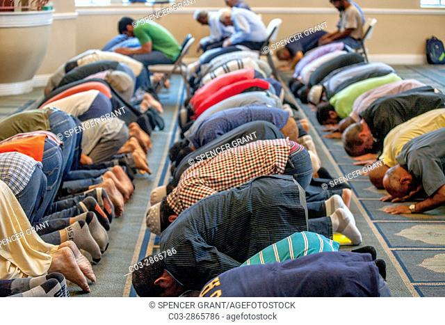 "Muslim men prostrate themselves in """"Sujood"""" prayer position with their faces on the Islamic patterned carpet at Friday afternoon prayers during religious..."