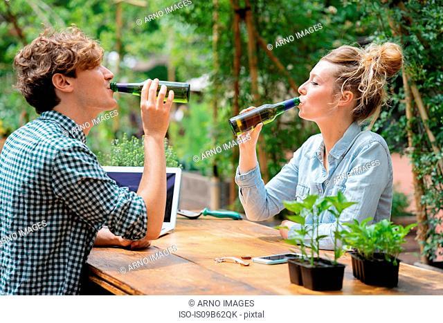 Couple drinking beer in garden