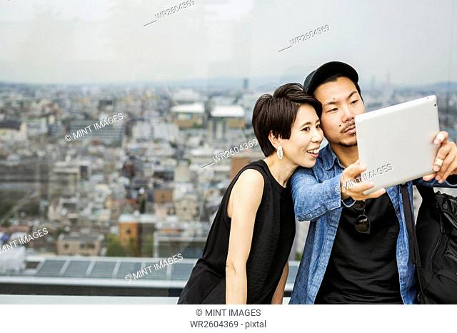 Two people, man and woman taking a selfie with a digital tablet, in front of a view over a large city
