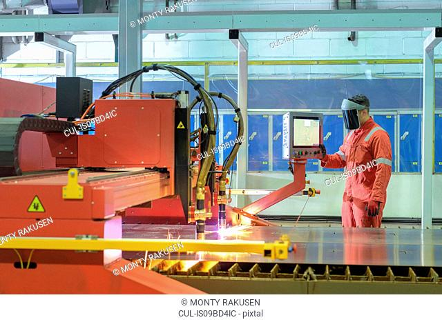 Worker operating plasma cutter in trailer factory