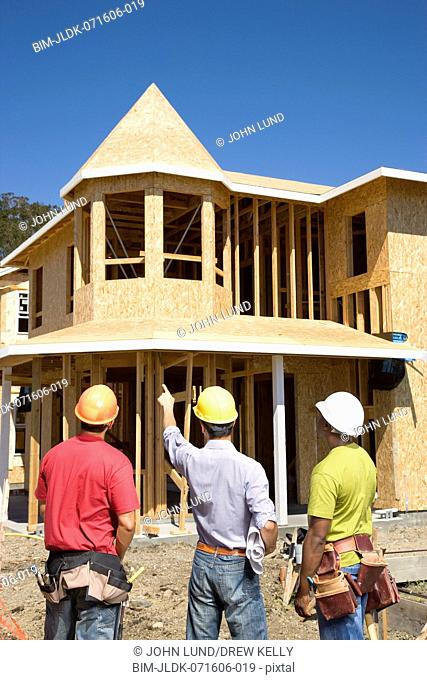 Male construction workers pointing at house under construction