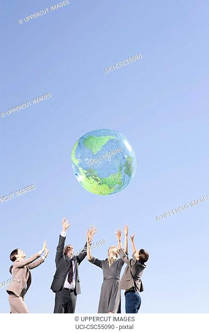 Businesspeople playing with globe ball