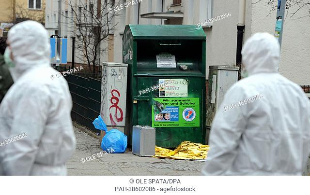 Forensic scientists stand in front of the used-clothes container where a dead baby was found in Berlin Neukoelln, Germany, 05 April 2013