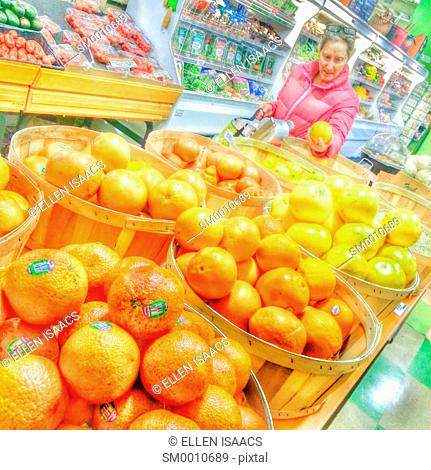 Caucasian woman age 55 shopping in the produce section of a grocery store holding a grapefruit, with buckets of oranges in the foreground and vegetables in the...