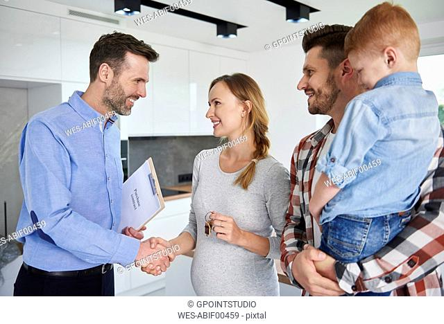 Family and real estate agent shaking hands in new apartment