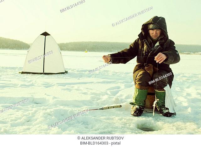 Caucasian man ice fishing on remote lake