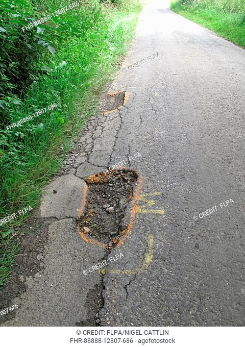Potholes in broken tarmac country road marked to warn cyclists of danger, Berkshire, England, July