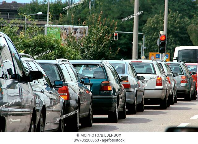 cars standing on the street at a red traffic light
