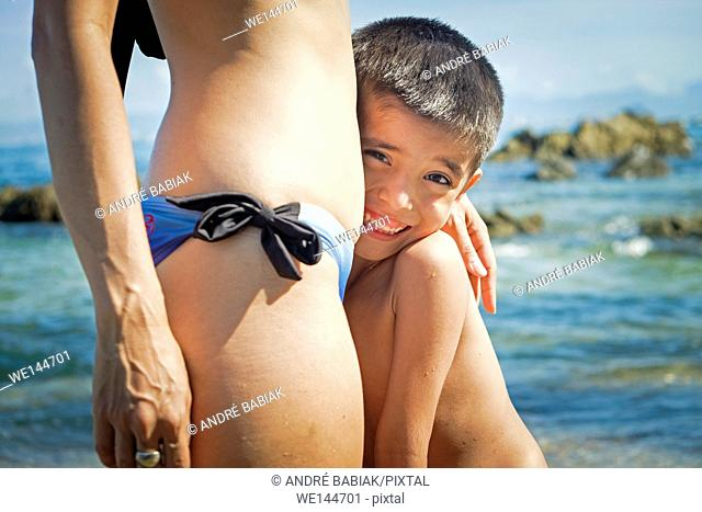 Young boy close to the body of his mother at a beach in Puerto Vallarta, Jalisco, Mexico