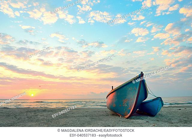 Fishing boats on the beach at sunrise