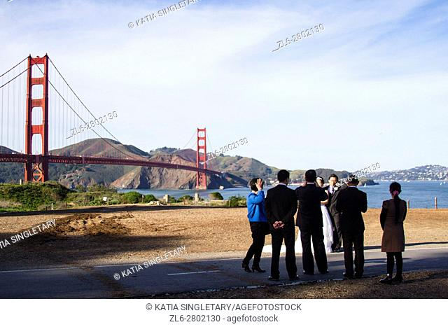 Bride, groom and groomsmen all dressed up in suits, and tuxedos, are getting their photo taken by the photographer View of Golden Gate Bridge in a sunny blue...