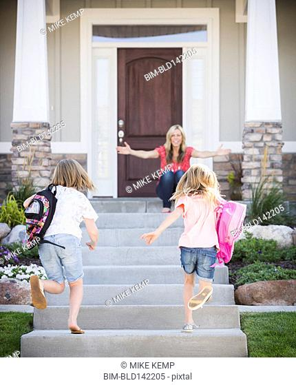 Caucasian mother greeting daughters returning home from school
