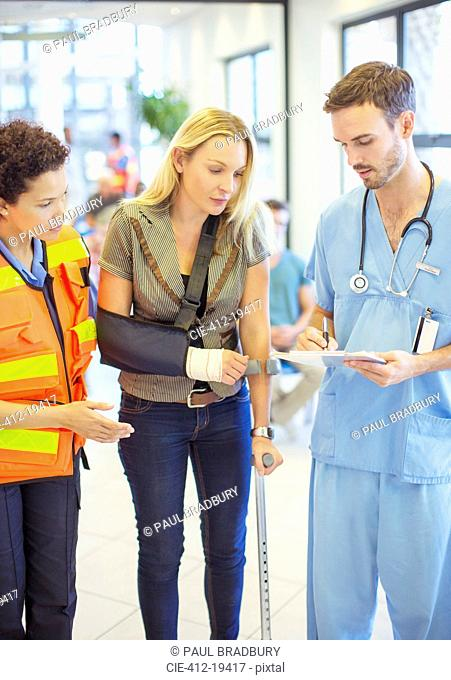 Nurse and paramedic talking to patient in hospital