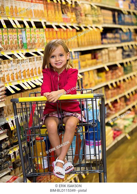Caucasian girl sitting in grocery cart
