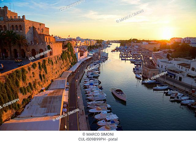 View of historic harbour waterfront and town hall at sunset, Ciutadella, Menorca, Balearic Islands, Spain