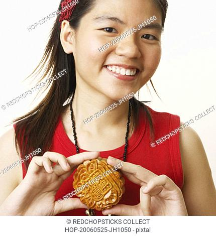Portrait of a young woman holding a cookie and smiling