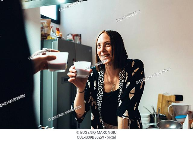 Young woman and boyfriend raising a coffee toast in kitchen