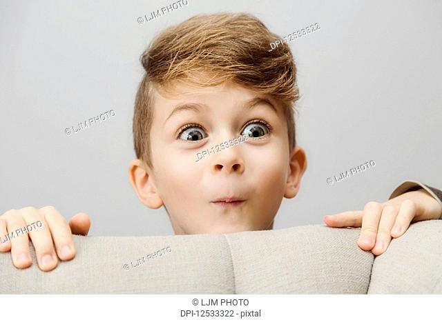 Portrait of a young boy peeking out from behind a couch with a silly wide-eyed facial expression; Langley, British Columbia, Canada