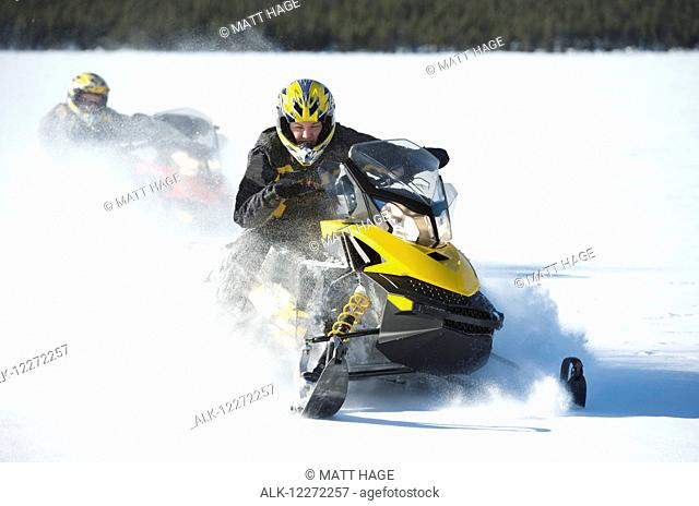 Two friends snowmachine through fresh snow on Little Harding Lake in Harding Lake State Recreation Area 45 miles south of Fairbanks in Interior Alaska