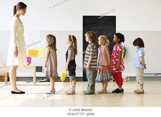 Preschool teacher with children standing in row