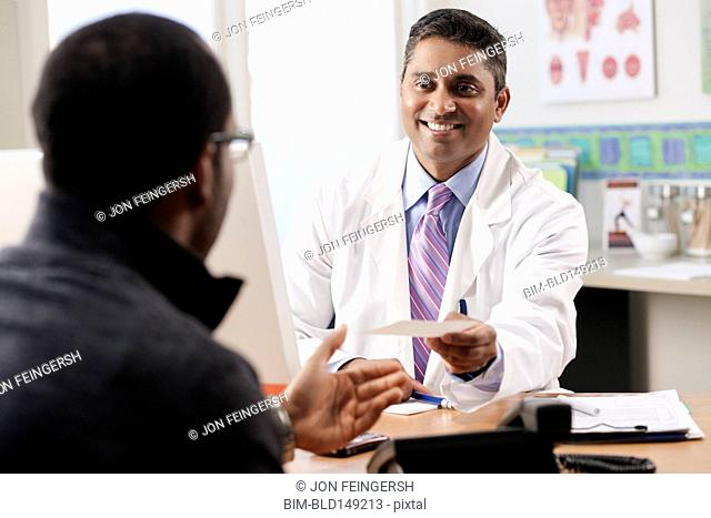 Doctor handing patient prescription in doctor's office