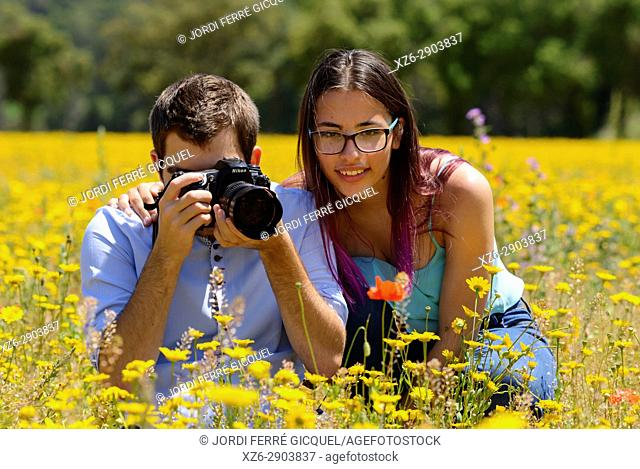 Young man and girl, photographing flowers in a field
