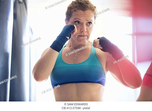 Determined female boxer with wrist wraps in fighting stance at gym