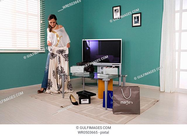 Woman in the living room with shopping bags holding a skirt