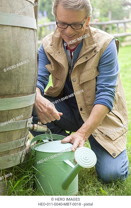 senior man filling watering can with water from a rain barrel