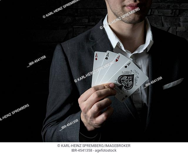 Card artist Jeremy Rowe holds playing cards in his hand, four aces, Germany
